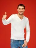 Hombre en el suéter caliente que muestra los pulgares para arriba Foto de archivo