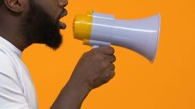 Hombre en el t-cortocircuito blanco que grita en el megáfono, conciencia del problema, aviso metrajes