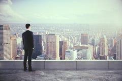Hombre en el tejado y mirada de la ciudad con los rascacielos Foto de archivo libre de regalías