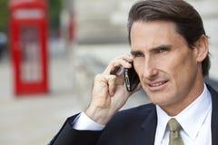 Hombre en el teléfono celular con la cabina de teléfonos roja de Londres Foto de archivo libre de regalías