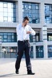 Hombre en el teléfono y controlar su reloj Imagen de archivo libre de regalías