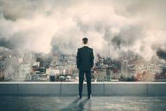 Hombre en el top de edificio y de mirar la ciudad de niebla Imágenes de archivo libres de regalías