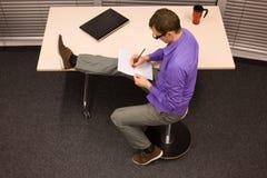 Hombre en el trabajo de oficina - estirar la pierna Foto de archivo libre de regalías