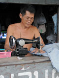 Hombre en el trabajo en un departamento de la ropa Foto de archivo libre de regalías