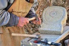 Hombre en el trabajo mientras que sculpting la piedra Imagen de archivo libre de regalías