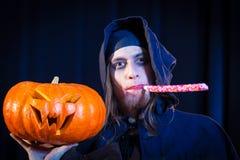 Hombre en el traje asustadizo de Halloween con la calabaza Foto de archivo libre de regalías