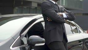 Hombre en el traje de negocios costoso que limpia el nuevo coche, feliz con la compra del auto metrajes