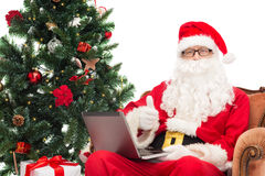 Hombre en el traje de Papá Noel con el ordenador portátil Fotos de archivo libres de regalías
