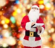 Hombre en el traje de Papá Noel con la libreta Fotografía de archivo