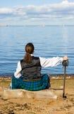 Hombre en el traje escocés que mira el mar Fotos de archivo libres de regalías