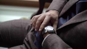 Hombre en el traje marrón que mira los relojes almacen de video