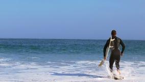 Hombre en el traje mojado que corre en el agua almacen de metraje de vídeo