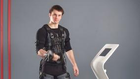 Hombre en el traje muscular eléctrico del estímulo que se coloca con pesas de gimnasia cerca de la tableta del ccsme y empuje en  almacen de metraje de vídeo