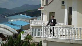 Hombre en el traje negro clásico que permanece en el balcón cerca del mar Hombre de negocios o novio almacen de video