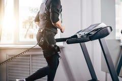 Hombre en el traje negro para el entrenamiento del ccsme que corre en la rueda de ardilla en el gimnasio Fotografía de archivo libre de regalías