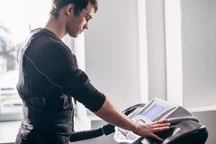 Hombre en el traje negro para el entrenamiento del ccsme que corre en la rueda de ardilla en el gimnasio Imágenes de archivo libres de regalías