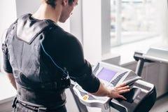 Hombre en el traje negro para el entrenamiento del ccsme que corre en la rueda de ardilla en el gimnasio Foto de archivo