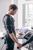 Hombre en el traje negro para el entrenamiento del ccsme que corre en la rueda de ardilla en el gimnasio Foto de archivo libre de regalías