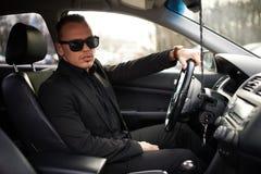 Hombre en el traje negro que se sienta detrás de la rueda fotografía de archivo