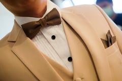 Hombre en el traje poner crema con la corbata de lazo marrón Imagen de archivo libre de regalías