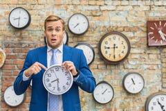 Hombre en el traje que coloca la pared cercana con los relojes imagen de archivo