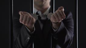 Hombre en el traje que muestra las manos en esposas detrás de barras, soborno, fraude financiero