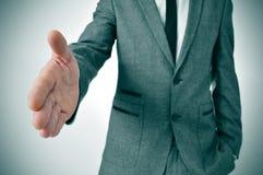Hombre en el traje que ofrece sacudir las manos Foto de archivo libre de regalías