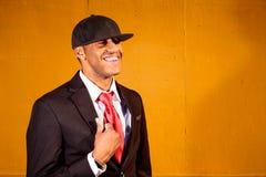 Hombre en el traje que se coloca delante de la sonrisa de madera amarilla de la pared Imagenes de archivo
