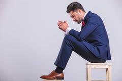 Hombre en el traje que se sienta en estudio con las palmas junto que parecen abajo Imagenes de archivo