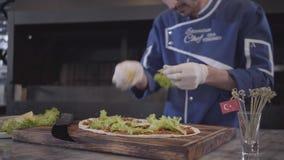 Hombre en el uniforme del cocinero que prepara el plato sabroso envuelto en lavash Mano del cocinero en las hojas de goma blancas almacen de video