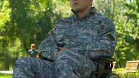 Hombre en el uniforme militar que se sienta en la silla de ruedas, descansando disfrutando de la naturaleza en parque almacen de video