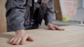 Hombre en el uniforme que toca con el panel de madera fresco de las manos almacen de video