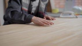 Hombre en el uniforme que toca con el panel de madera fresco de las manos almacen de metraje de vídeo