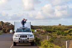 Hombre en el viaje de la caravana que toma las fotos del techo corredizo del coche foto de archivo libre de regalías