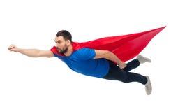 Hombre en el vuelo rojo del cabo del super héroe en el aire Imagenes de archivo