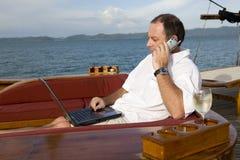 Hombre en el yate con el teléfono y la computadora portátil Fotos de archivo