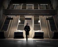 Hombre en escaleras móviles Imagenes de archivo