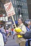 Hombre en esquina de calle con la muestra durante el maratón de la ciudad de NY, NY Imagen de archivo libre de regalías