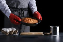 hombre en fondo oscuro del potholder de la empanada roja de la tenencia y aislado en negro concepto de la receta con los ingredie foto de archivo