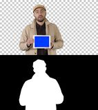 Hombre en foso que camina y que sostiene la tableta con la maqueta de la pantalla azul que presenta algo, Alpha Channel fotos de archivo