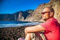 Hombre en gafas de sol que goza de la playa hermosa Playa de los Guios Fotos de archivo