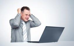 Hombre en ganchos agarradores del horror su cabeza que mira la pantalla del ordenador portátil Concepto de problemas del ordenado fotografía de archivo libre de regalías