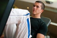 Hombre en gimnasia en el ejercicio de la máquina Foto de archivo libre de regalías