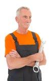 Hombre en guardapolvo anaranjado y gris con la llave Imagen de archivo libre de regalías