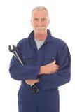 Hombre en guardapolvo azul con la llave Imagen de archivo