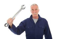 Hombre en guardapolvo azul con la llave Fotografía de archivo libre de regalías