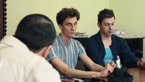 Hombre en hablar enojado de la red de pelo con dos visitantes en la reunión de la oficina almacen de metraje de vídeo
