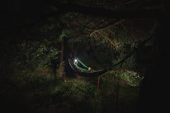 Hombre en hamaca debajo de árboles en la noche Imagenes de archivo