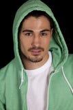 Hombre en hoodie verde en negro Imagenes de archivo
