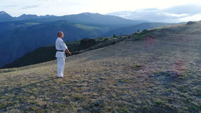 Hombre en karate del entrenamiento del kimono blanco y de la correa negra en fondo de la montaña cámara lenta aérea 4k